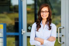 Woman standing outside her house and smiling Stock Photos