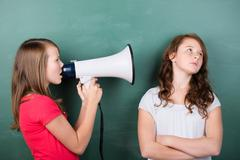 Girl trying to make herself heard with a megaphone Stock Photos