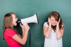 young schoolgirl making herself loudly heard - stock photo