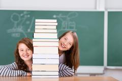 Schoolgirls peeking behind a pile of books Stock Photos