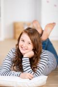 smiling young teenage girl laying on the floor - stock photo