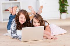 two amused young teenage girls using a laptop - stock photo