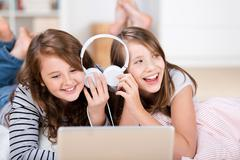 two young girls share headphones to listen music - stock photo