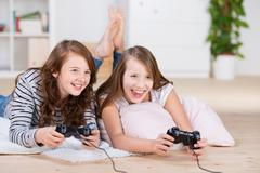 Two young girls happily playing video games Stock Photos
