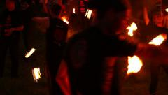 Multiple artists spin twist dance with fire pois, chains, fans, sticks Stock Footage