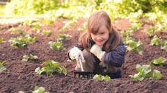 The llittle girl weeds potato and loosens the earth, hills Stock Footage