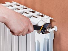 adjusting heating radiator - stock photo