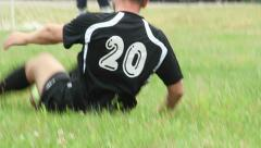 Amateur player falls down on ground trying to get the ball Stock Footage