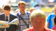 Stock Video Footage of man with  newspaper in crowd  .  Slow motion