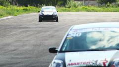 Steering race cars and track tarmac, drivers pass by - stock footage
