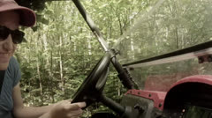 A woman driving through a dense forrest Stock Footage