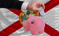 funding euro into piggy rich bank flag of american state of florida - stock photo