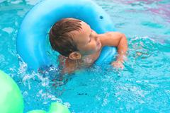 Preschool boy swims in pool on summer vacations Stock Photos