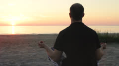 Young Man Meditating by the Sea Stock Footage