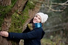 woman in winter clothes embracing tree - stock photo
