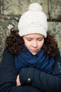 Woman in winter clothes shivering against stonewall Stock Photos