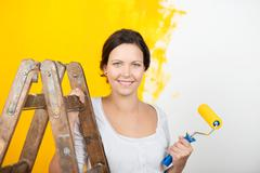 woman with ladder holding paintroller against wall - stock photo
