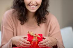 Excited woman with a small red gift box Stock Photos