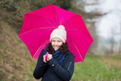 Walking under a pink umbrella Stock Photos