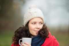 woman in winter clothes looking away while holding coffee mug - stock photo