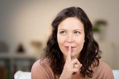woman with finger on lips at home - stock photo