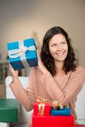 happy woman guessing the contents of her gifts - stock photo