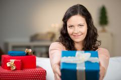 Woman giving christmas gift at home Stock Photos