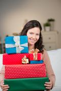 smiling woman with a stack of gift boxes - stock photo