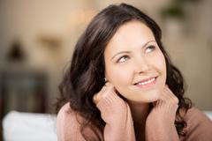 thoughtful young woman looking up in house - stock photo