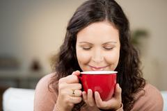 woman with eyes closed drinking coffee at home - stock photo