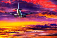 Passenger aircraft on colorful sky Stock Photos
