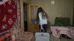 A woman with a suitcase out of the house Stock Footage