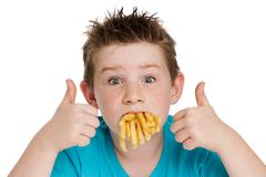 young boy with mouth full of chips - stock photo
