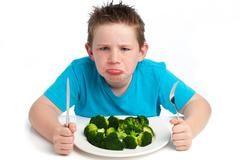 Grumpy young boy not happy about eating broccoli. Stock Photos
