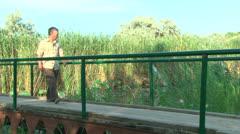 An elderly man goes on a wooden bridge Stock Footage