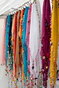Colorful beaded scarves hang in vendor booth at festival Stock Photos