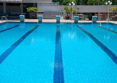 blue swimming pool and starting places at sport center - stock photo