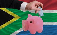 funding euro into piggy rich bank national flag of south africa - stock photo