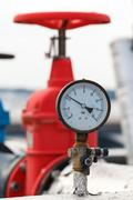 Manometer, red valve on hot pipe Stock Photos