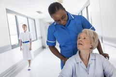 Stock Photo of senior female patient in wheelchair & nurse in hospital
