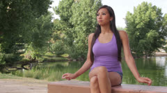 Asian Girl Sits Contemplative by Water at Green Park - stock footage