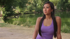Stock Video Footage of Asian Girl Sits Contemplative by Water at Green Park
