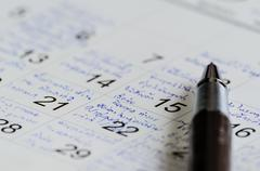 pen on calendar - stock photo