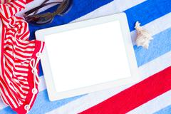 Tablet on beach towels with sunbathing accessories Stock Photos