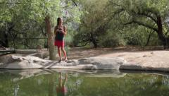 Asian Woman Casts Reflection on Water LS Stock Footage