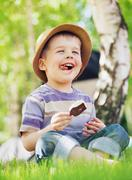 satisfied little boy consuming an ice cream - stock photo