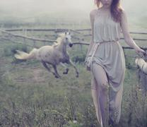 delicate brunette posing with horse in the background - stock photo