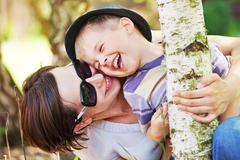 laughing small boy hugged by his mother - stock photo