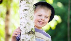 cheerful boy hiding himself in the garden - stock photo