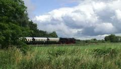 Steam train riding in countryside - cumulus clouds Stock Footage